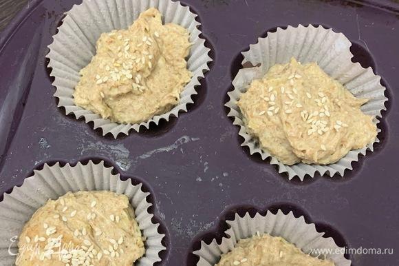 Смазываем формочки для запекания растительным маслом, либо можно использовать бумажные формы для кексов. Готовое тесто выкладываем на смазанную растительным маслом поверхность, разделяем на порционные части, раскладываем по формам, посыпаем кунжутом ТМ «Националь» и дает подойти еще минут 10–15. Выпекаем в горячей духовке около 20–25 минут.