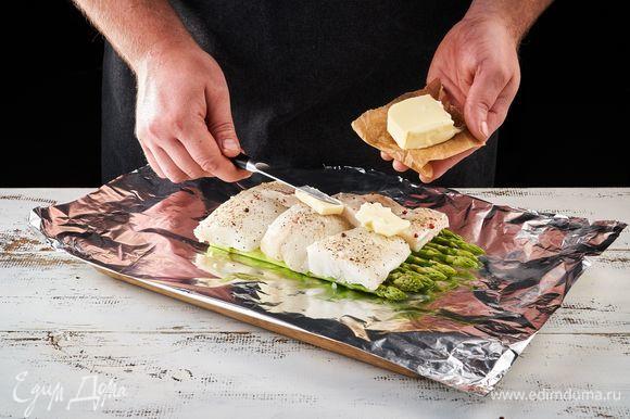 Выложите в фольгу сливочное масло, рыбу, спаржу, мини-кукурузу и черри.