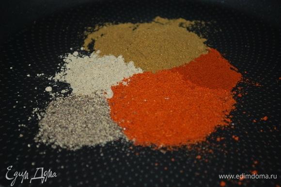На разогретую сковороду добавьте все специи и растительное масло. Можно добавить сухой чеснок, по желанию.