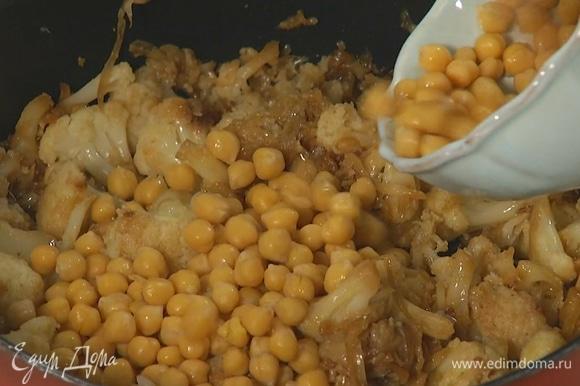 Цветную капусту разобрать на небольшие соцветия, выложить к луку с чесноком, посолить и обжарить до готовности, затем добавить 2 ст. ложки оливкового масла, нут без жидкости и все перемешать.