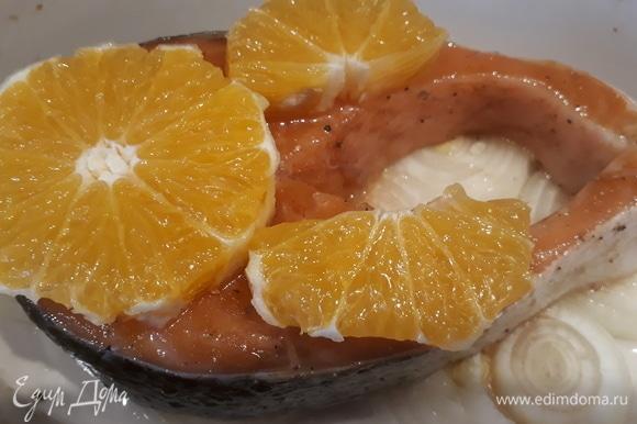 Очищаем 2 дольки апельсина и кладем их на семгу.
