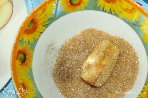 В тарелке смешиваем сахар и корицу. И обваливаем яблочные дольки.