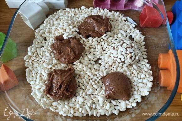 В миску насыпать воздушный рис. С помощью ложки выложить небольшими порциями тесто и сформировать шарики.