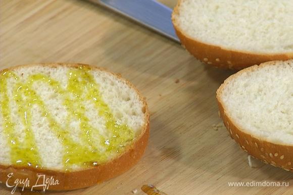 Булочки для бургера разрезать пополам, нижнюю часть смазать оливковым маслом.
