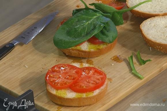 Помидор нарезать кружками, выложить на нижнюю часть булочек и накрыть листьями шпината.