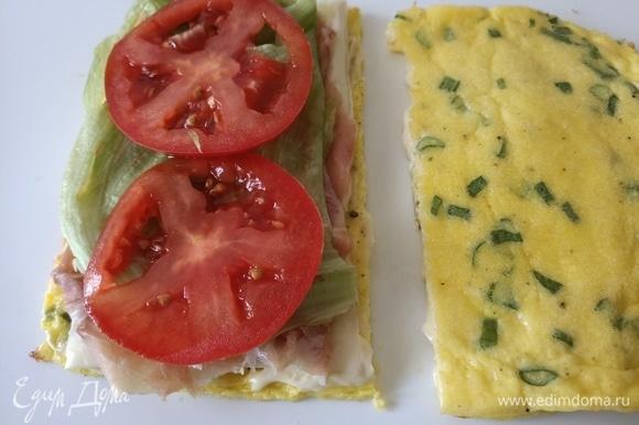 Сверху выложить сыр пластинками, ветчину, лист салата и помидор. Накрыть второй частью омлета. Разрезать.