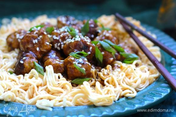 Слейте из лапши воду и добавьте лапшу в сковороду, перемешайте и посыпьте зеленым луком, кунжутом. Подавайте мясные фрикадельки с лапшой в азиатском стиле к столу. 