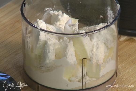 Предварительно охлажденное оставшееся сливочное масло порезать на небольшие кусочки и выложить в чашу блендера, добавить сахар, муку и измельчить все в крошку.