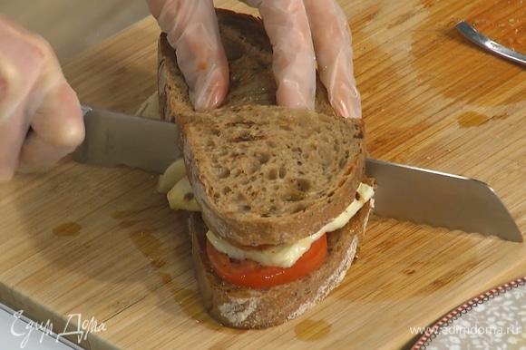 Второй кусок хлеба смазать пастой харисса и полить оливковым маслом, затем накрыть им бутерброд, сильно прижать и разрезать пополам.