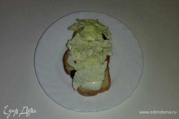 Затем выкладываем на каждый кусочек белого хлеба слой нарезанных листьев китайского салата.