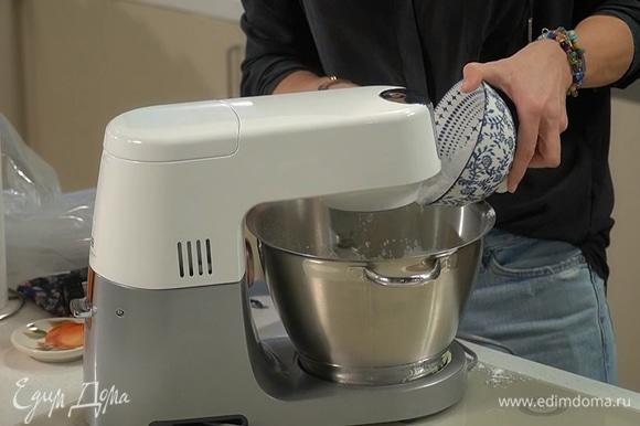 Белки поместить в чашу комбайна и взбить на большой скорости в крепкую пену, затем, не выключая комбайна, небольшими порциями ввести 150 г сахарной пудры и взбивать белки еще минимум 10 минут.