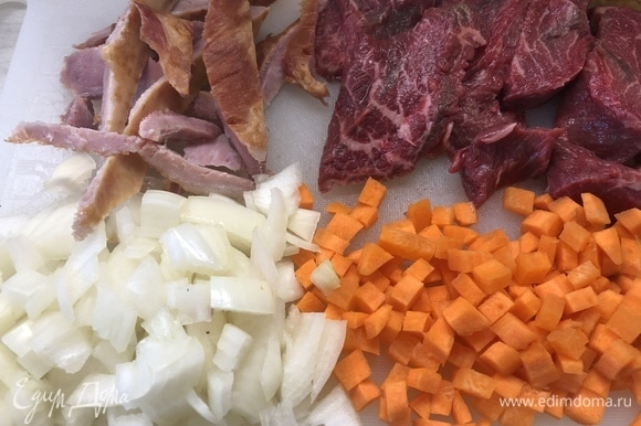 Нарежьте мясо на небольшие стейки, лук и морковь — небольшими кубиками.
