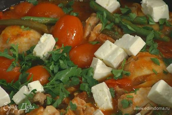 Выложить курицу с овощами на блюдо, сверху разложить фету, посыпать измельченной петрушкой.