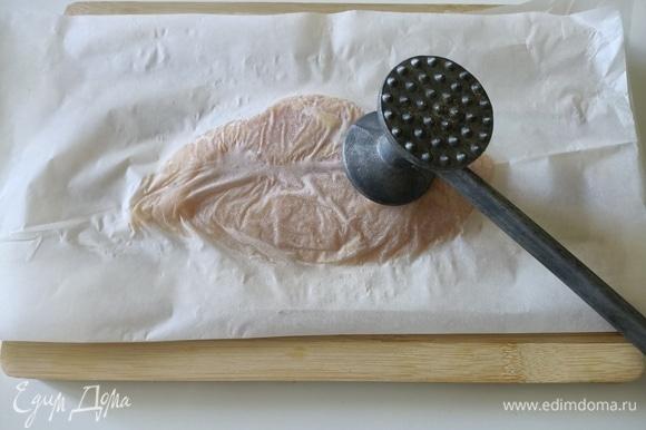 Куриное филе положить между листами пергаментной бумаги и отбить.