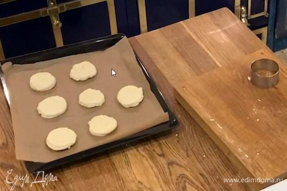 Сформировать из теста толстый пласт, кондитерским кольцом вырезать лепешки и выложить на противень, застеленный бумагой для выпечки.