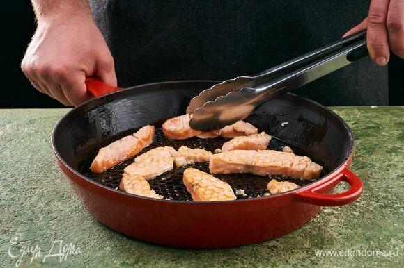 Лосося нарежьте полосками. Разогрейте сковороду с оливковым маслом и выложите рыбу.