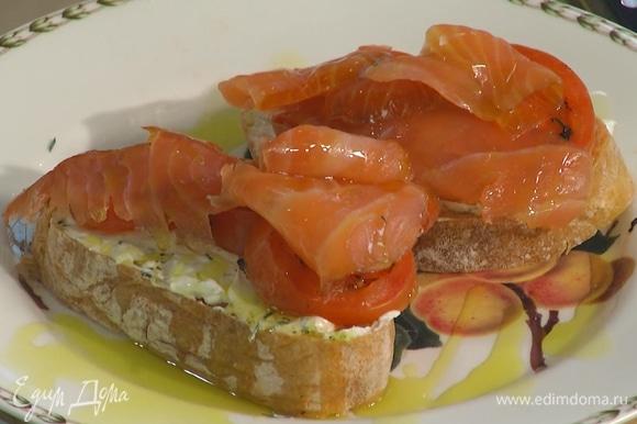 Намазать подсушенный хлеб заправленным сливочным сыром, сверху разложить кусочки помидора и ломтики лосося, полить оставшимся оливковым маслом.
