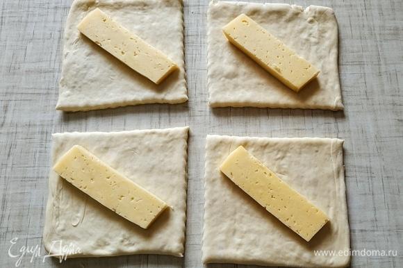 Слоеное дрожжевое тесто разрезать на 4 части. Положить кусочек сыра.