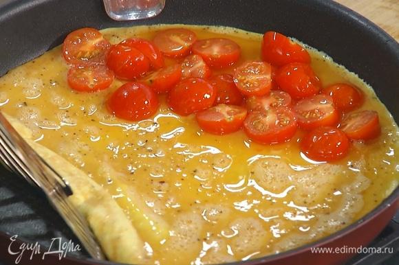Влить яичную смесь в сковороду и прогревать на среднем огне. Когда омлет схватится по краям, на одну его половину выложить припущенные помидоры, накрыть второй половиной и жарить до готовности.