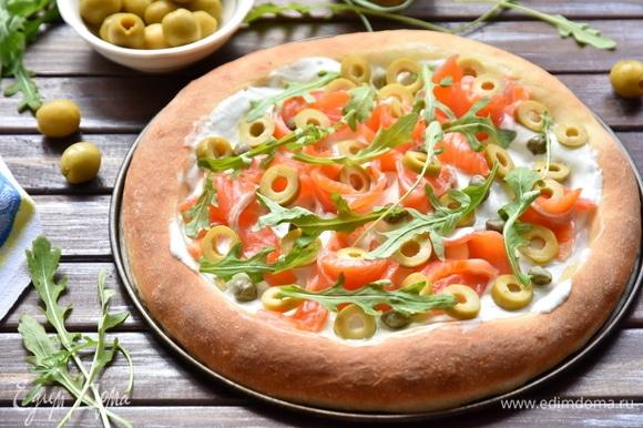 Выпекать тесто 12 минут в разогретой до 250°C духовке. Смазать центр горячей лепешки сметаной. Выложить ломтики лосося, оливки, каперсы и руколу.