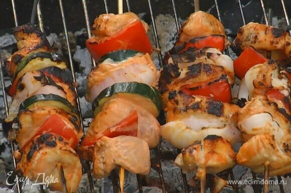 Шпажки предварительно замочить в воде, затем нанизать на них кусочки курицы, сладкий перец, красный лук и цукини и пожарить на гриле со всех сторон до готовности.