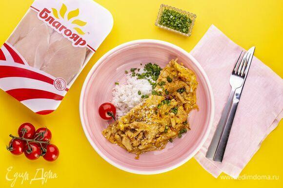 Выложите на тарелку горкой отваренный рис, сверху омлет с курицей. Посыпьте оякодон измельченным зеленым луком кунжутом по желанию.