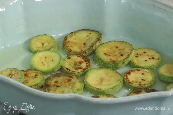 Форму для выпекания смазать оливковым маслом, на дно уложить обжаренные кабачки.