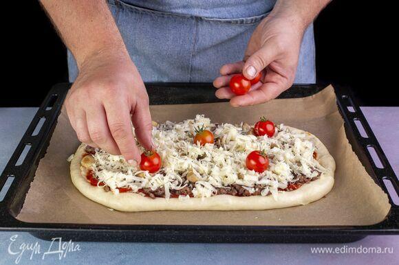 Выложите помидоры черри. Загните края пиццы по бокам и выпекайте в разогретой до 220 °С духовке 10–12 минут.