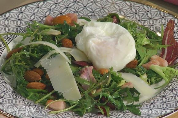 Разложить салат на тарелки, посыпать кусочками грудинки, миндалем и сыром, сверху выложить яйцо.