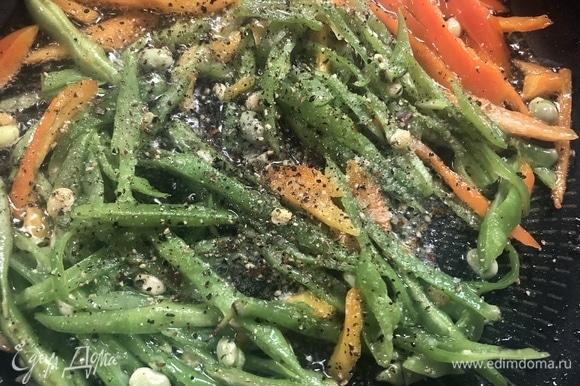 На разогретую сковороду с маслом отправляем фасоль и перец, солим, перчим, жарим 1–2 минуты.