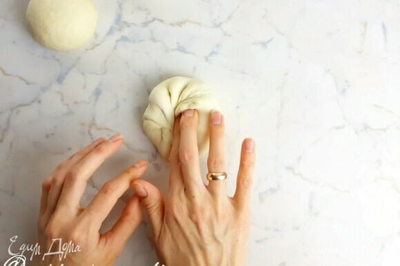 Смешиваем до растворения теплую воду (~37°C), дрожжи, соль, сахар и оливковое масло. Всыпаем просеянную муку. Хорошо вымешиваем тесто руками минут 7, до гладкости. Кладем его в чашку, накрываем пленкой и даем подняться в полтора раза (40–60 минут). Делим тесто на кусочки по 100 г. Формируем шарики. Для этого у каждого кусочка теста все края загибаем в центр.