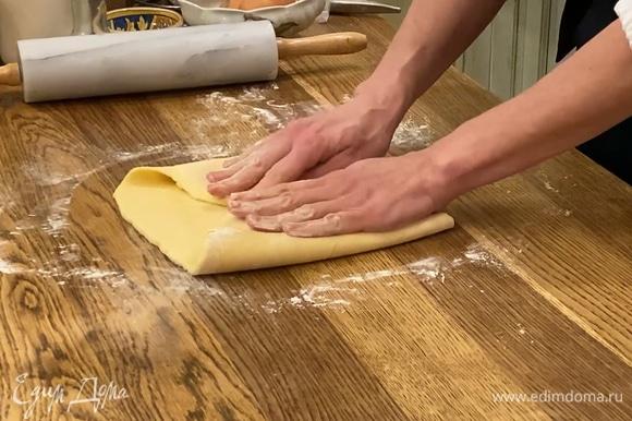 Охлажденное тесто раскатать в прямоугольник и завернуть края к центру, затем сложить пласт вдвое, так чтобы получилась «книжка». Убрать тесто в пакет и еще на 15 минут поместить в морозилку.
