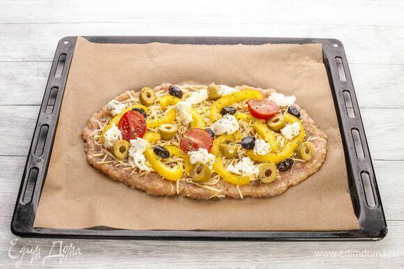 Болгарский перец нарежьте соломкой, черри — пополам, маслины — колечками, моцареллу порвите на мелкие кусочки. Все выложите на пиццу. Посыпьте прованскими травами. Запекайте пиццу в духовке при 200 °С 15 минут.