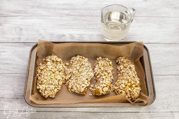 Противень застелите пекарской бумагой и сбрызните небольшим количеством растительного масла. Выложите курицу. Запекайте в духовке при 200 °С около 20–25 минут.