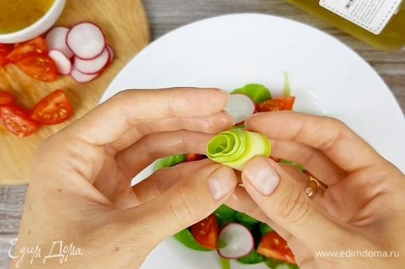 В тарелку выкладываем зелень, редис, томаты. Из слайсов кабачка крутим рулетики.