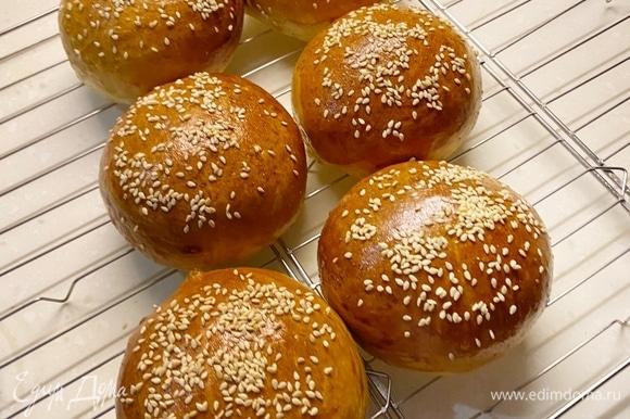 Поделить тесто на шесть равных частей (лучше на весах) и сформировать булочки. Выложить на противень, накрыть пленкой и расстаивать в духовке при 35–40°C примерно 25–35 минут. Они должны увеличиться в два раза. Затем смазать яйцом, посыпать кунжутом и выпекать около 20 минут при 180–190°C, до румяности.
