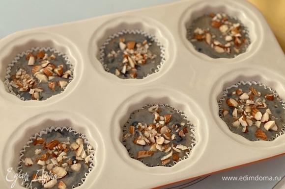 Разложить тесто в формы ложкой, заполнив их до самого верха (!). Сверху выложить порубленные любимые орехи, смешанные с сахаром. Выпекать 5 минут при 220°C, далее снизить до 175°C, выпекать еще 18–20 минут.