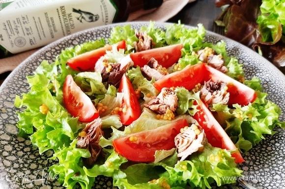 На блюдо выкладываем листья салата, сверху — дольки томата и кусочки тунца. Поливаем заправкой. Подаем салат сразу. Приятного аппетита!