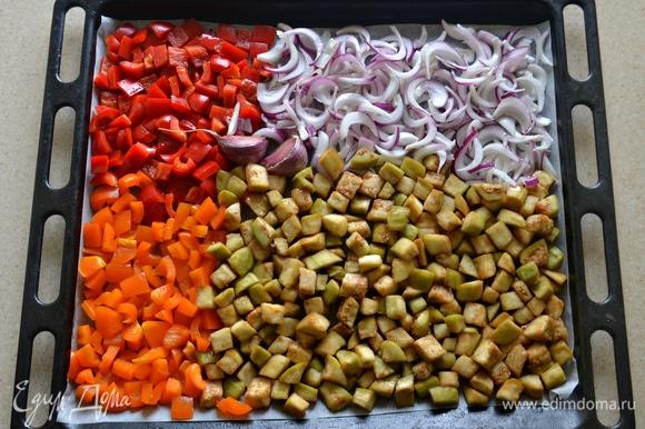 Перец очистить от семян и нарезать кубиками. Лук очистить и нарезать перьями. Уложить овощи вместе с неочищенными зубчиками чеснока на противень, застеленный пекарской бумагой. Сбрызнуть оливковым маслом и запекать при 180°C около 40 минут, пока овощи не станут мягкими. Во время запекания овощи пару раз нужно аккуратно перемешать.