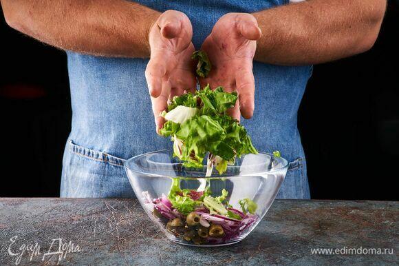 В салатник выложите салатный микс, вяленые томаты, оливки.