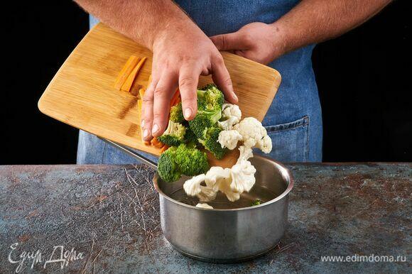 Брокколи, капусту и морковь добавьте в кастрюлю и проварите в течение 5 минут.