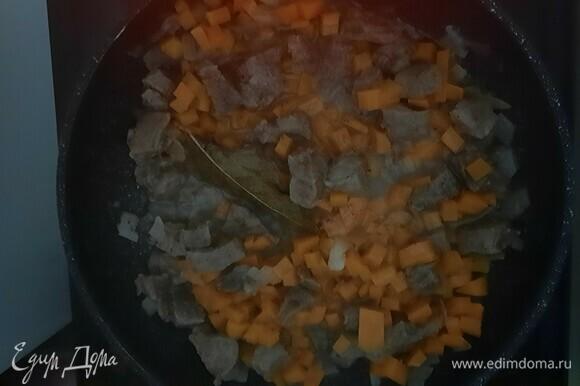 Добавим сначала морковь, а затем шампиньоны с перцем к мясу. Тушим еще 10–15 минут.