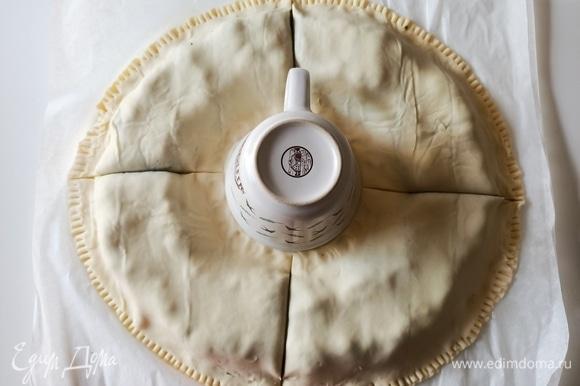 Тесто без начинки смазываем водой и накрываем вторым пластом слоеного теста, защипываем концы. В центр ставим чашку и разрезаем тесто на четыре части.