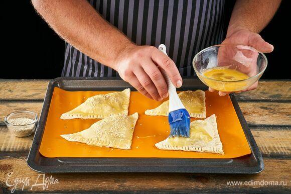 Пирожки выложите на противень, застеленный пергаментом и смазанный растительным маслом. Яйцо взбейте вилкой, а затем смажьте этой смесью пирожки. Сверху посыпьте кунжутом. Выпекайте в духовке при 180°C около 20 минут.