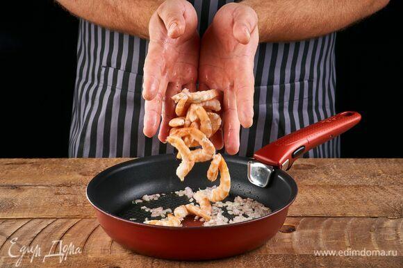 Обжарьте лук на сковороде в небольшом количестве растительного масла. Добавьте очищенные креветки. Обжарьте вместе луком около 2 минут.