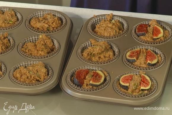 Формочки для кексов заполнить тестом на 3/4 от общего объема, сверху разложить дольки инжира.