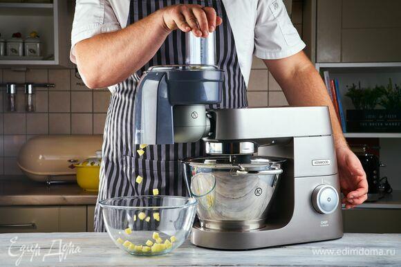 Овощи для супа очистите. Установите на кухонную машину насадку-овощерезку и нарежьте кубиками картофель и очищенный помидор.
