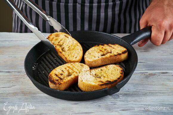 Чиабатту нарежьте кусочками толщиной 1 см, сбрызните оливковым маслом каждый кусочек и подсушите на сковороде-гриль.