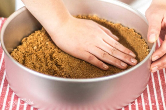 Смазать форму сливочным маслом (я использовала силиконовую форму). Распределить массу с печеньем по дну (толщина около 2 см), сделать бортик. Поставить в духовку и выпекать при 180°C около 15 минут. Дать коржу остыть 10–15 минут.