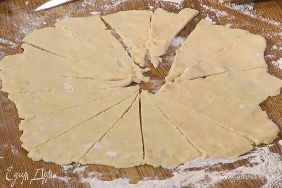 Половину теста выложить на рабочую поверхность, присыпанную оставшейся мукой, и раскатать в круг толщиной 3–4 мм, а затем разрезать на 16 секторов-треугольников.